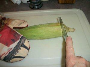 Slice off husks at beginning of corn cob.