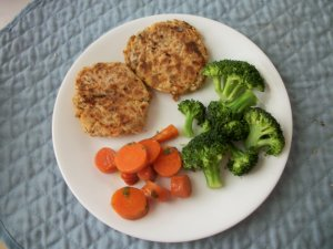 Salmon croquettes served with steamed broccoli and herbed carrots.